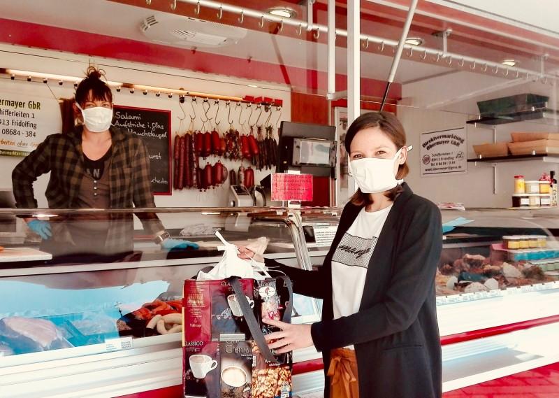 """Maria Meinel, Mitarbeiterin der Wirtschaftsförderungs GmbH übergibt an Christine Obermayer, 1. Vorsitzende der Direktvermarkter Traunstein, eine Lieferung von sogenannten """"Community-Masken"""". ©Landratsamt Traunstein"""