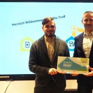 """© Landratsamt Traunstein: Robert Ossenkopp (links), Mobilreferent des Projekts """"Digitale Nachbarschaft"""", überreicht Freiwilligenagenturleiter Florian Seestaller die offizielle DiNa-Treff-Plakette."""